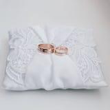 Alianças de casamento com diamantes em um descanso de seda branco com laços Fotografia de Stock Royalty Free