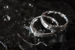 Alianças de casamento com gotas da água em uma obscuridade Imagem de Stock