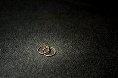 Alianças de casamento com luz do ouro de ponto Fotos de Stock Royalty Free