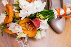 Alianças de casamento com ramalhete e sapatas imagens de stock