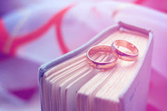 Alianças de casamento com um livro do vintage Fotografia de Stock