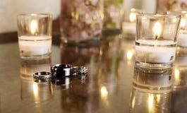 Alianças de casamento com velas brancas Fotos de Stock Royalty Free