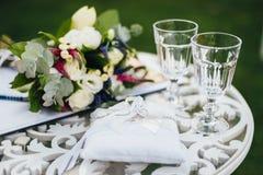 Alianças de casamento com vidros e ramalhete na tabela da cerimônia imagens de stock