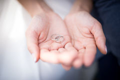 Alianças de casamento de prata nas mãos da mulher fotografia de stock royalty free