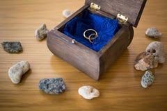 Alianças de casamento dentro da caixa de madeira aberta com pedras ao redor ceremony imagens de stock