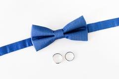 Alianças de casamento do ouro e bowtie do noivo Fotos de Stock