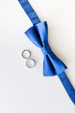 Alianças de casamento do ouro e bowtie do noivo Fotografia de Stock