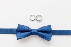Alianças de casamento do ouro e bowtie do noivo Fotografia de Stock Royalty Free