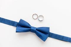 Alianças de casamento do ouro e bowtie do noivo Imagem de Stock