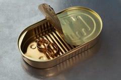 Alianças de casamento do ouro em uma lata Fotos de Stock