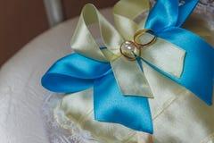 Alianças de casamento do ouro na almofada de alfinetes Imagem de Stock
