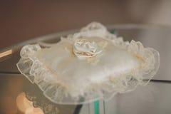Alianças de casamento do ouro na almofada de alfinetes Foto de Stock