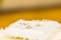 Alianças de casamento do ouro na almofada de alfinetes Fotografia de Stock
