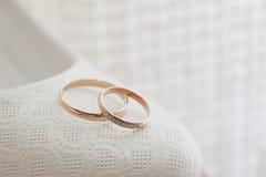 Alianças de casamento do ouro na almofada de alfinetes Fotos de Stock