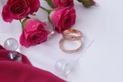 Alianças de casamento do ouro na tela cor-de-rosa com fita e as rosas brancas fotos de stock royalty free
