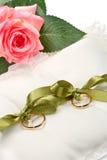 Alianças de casamento do ouro no descanso branco Imagem de Stock