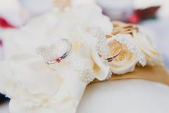 Alianças de casamento do ouro no descanso branco Imagens de Stock