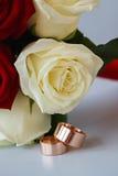 Alianças de casamento do ouro no ramalhete das flores para a noiva Fotografia de Stock