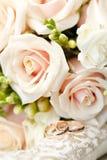 Alianças de casamento do ouro no ramalhete das flores para a noiva Imagens de Stock