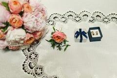 Alianças de casamento douradas em uma caixa com fita e fim cor-de-rosa do ramalhete Fotos de Stock Royalty Free