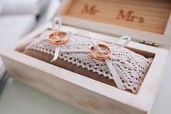 Alianças de casamento douradas em uma caixa de madeira branca Decoração do casamento Símbolo da família, da unidade e do amor Fotos de Stock Royalty Free