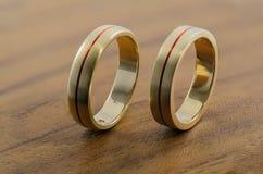 Alianças de casamento douradas na superfície de madeira Imagem de Stock Royalty Free