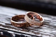 Alianças de casamento douradas no backrgound de madeira Fotografia de Stock