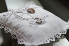 Alianças de casamento douradas no descanso do cetim na igreja imagens de stock royalty free