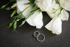 Alianças de casamento douradas no fundo cinzento com flores brancas imagens de stock royalty free