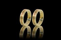 Alianças de casamento douradas no vidro preto Fotos de Stock Royalty Free