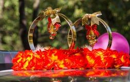 Alianças de casamento e flores unidas ao carro Imagem de Stock