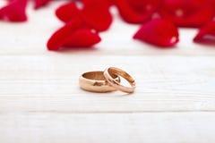 Alianças de casamento e ramalhete do casamento das pétalas de rosas vermelhas Fotos de Stock Royalty Free