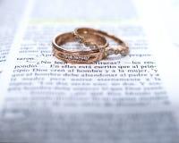 Alianças de casamento e scripture espanhol da Bíblia fotos de stock royalty free