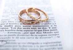 Alianças de casamento e scripture espanhol da Bíblia imagem de stock