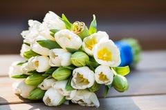 Alianças de casamento e tulipas brancas fotos de stock royalty free