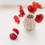 Alianças de casamento e vaso com flores da papoila Imagem de Stock