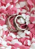 Alianças de casamento em corações doces do açúcar fotografia de stock royalty free
