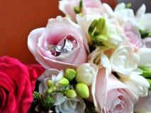 Alianças de casamento em flores Fotografia de Stock Royalty Free