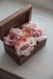 Alianças de casamento em flores na caixa de madeira rústica velha para a cerimônia de casamento Fotografia de Stock Royalty Free
