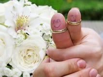 Alianças de casamento em seus noivos dos marrieds dos povos dos dedos, homens pequenos engraçados pintados Fotos de Stock