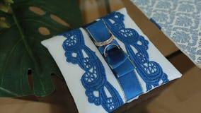 Alianças de casamento em um coxim com testes padrões azuis filme