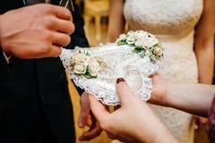 Alianças de casamento em um descanso coração-dado forma no fundo dos noivos imagem de stock royalty free