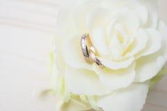 Alianças de casamento em um fim da flor acima Foto de Stock