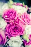 Alianças de casamento em um fundo de rosas cor-de-rosa Fotografia de Stock