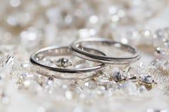Alianças de casamento em um fundo dos grânulos e dos cristais Imagem de Stock