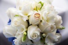 Alianças de casamento em um ramalhete das flores fotografia de stock royalty free