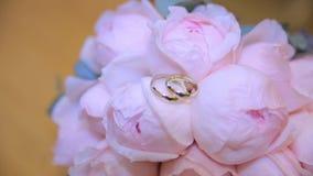Alianças de casamento em um ramalhete das flores brancas Alianças de casamento e ramalhete da obscuridade - flor azul Fim acima c vídeos de arquivo