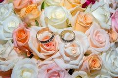 Alianças de casamento em um ramalhete das rosas Fotos de Stock Royalty Free