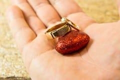 Alianças de casamento em uma pedra natural com inclusões do ouro nativo Mãos e corações da oferta Imagem de Stock Royalty Free