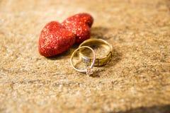 Alianças de casamento em uma pedra natural com inclusões do ouro nativo Mãos e corações da oferta Imagem de Stock